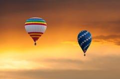 Deux ballons à air chauds en vol sur le ciel de coucher du soleil Images stock