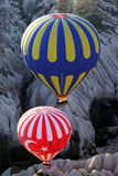 Deux ballons à air chauds flottent en bas d'une vallée près de Goreme dans la région de Cappadocia de la Turquie Photo libre de droits