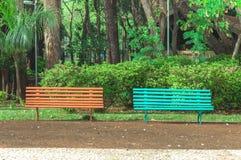 Deux bancs côte à côte sur une place avec des arbres et un beau fond vert de végétation Photographie stock