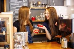 Deux barman heureux de filles tenant des butées toriques dans leurs mains Images libres de droits