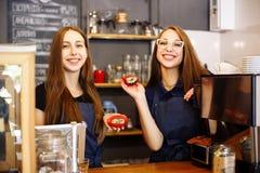 Deux barman heureux de filles tenant des butées toriques dans leurs mains Photos stock