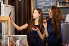 Deux barman heureux de filles tenant des butées toriques dans leurs mains et faisant des selfies Photographie stock libre de droits