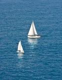 Deux bateaux à voiles blancs sur l'eau bleu-foncé Photographie stock