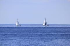 Deux bateaux à voiles sur l'horizon de mer ouverte Photographie stock libre de droits