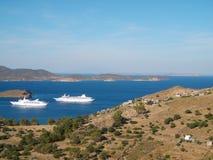 Deux bateaux de croisière entrant dans ville portuaire de Skala dans Patmos, Grèce images stock