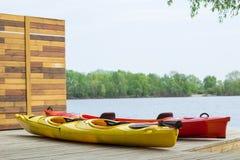 Deux bateaux de kayak sur la plate-forme à la station près de la rivière Image libre de droits