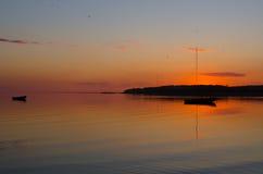 Deux bateaux de pêche dans la baie pendant un coucher du soleil orange coloré Images stock