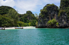 Deux bateaux sur la petite, reculée plage des arbres ont couvert l'île Photographie stock libre de droits