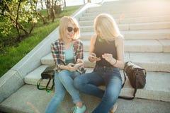 Deux beaux étudiants observant le contenu de media sur la ligne dans le téléphone intelligent en parc Images stock