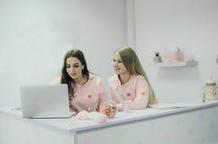 Deux beaux administrateurs de jeunes filles tenant l'ordinateur portable proche Image stock