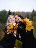 Deux beaux amie avec des lames d'automne Photo stock