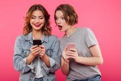 Deux beaux amis de dames causant par des téléphones Image libre de droits