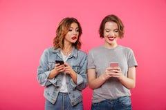 Deux beaux amis de dames causant par des téléphones Photo libre de droits