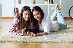 Deux beaux amis de jeune femme à l'aide du comprimé numérique à la maison Images stock