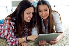 Deux beaux amis de jeune femme à l'aide du comprimé numérique à la maison Photos stock