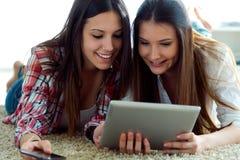 Deux beaux amis de jeune femme à l'aide du comprimé numérique à la maison Photographie stock