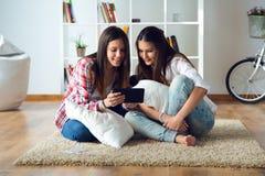 Deux beaux amis de jeune femme à l'aide du comprimé numérique à la maison Photo stock