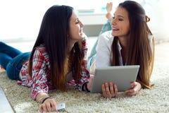 Deux beaux amis de jeune femme à l'aide du comprimé numérique à la maison Images libres de droits