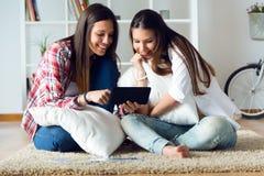 Deux beaux amis de jeune femme à l'aide du comprimé numérique à la maison Photographie stock libre de droits