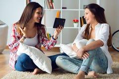 Deux beaux amis de jeune femme à l'aide du comprimé numérique à la maison Image stock
