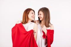 Deux beaux amis féminins les couvrant individu de couverture rouge Photographie stock libre de droits