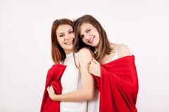 Deux beaux amis féminins les couvrant individu de couverture rouge Images stock