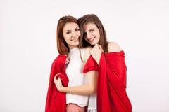Deux beaux amis féminins les couvrant individu de couverture rouge Photos stock