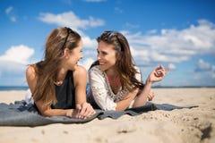 Deux beaux amis féminins parlant sur la plage Photo stock