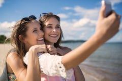 Deux beaux amis féminins prenant le selfie sur la plage Image stock