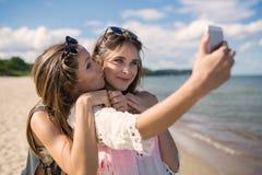 Deux beaux amis féminins prenant le selfie sur la plage ayant l'amusement Image stock