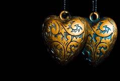 Deux beaux coeurs en métal avec l'au sol de dos d'obscurité Image libre de droits