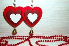 Deux beaux coeurs romantiques et perles rouges sur un backgroun léger Photographie stock libre de droits