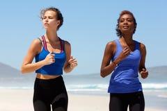 Deux beaux coureurs féminins s'exerçant sur la plage Images stock
