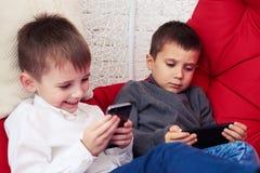 Deux beaux enfants de mêmes parents à l'aide des téléphones tout en se reposant dans un Han de oscillation Photographie stock