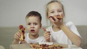 Deux beaux, enfants drôles mangeant de la pizza Le garçon sourit, la fille rit et montre son doigt comme Concept : délicieux banque de vidéos