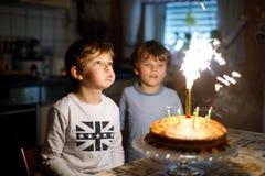 Deux beaux enfants, petits garçons préscolaires célébrant l'anniversaire et soufflant des bougies Image libre de droits