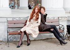Deux beaux femmes en stationnement s'asseyent sur un banc Photos stock