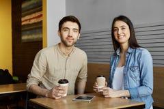 Deux beaux jeunes étudiants s'asseyant dans le cafétéria, cacao potable, sourire, regardant in camera posant pour l'université Photos stock