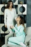 Deux beaux jeunes amis féminins dans le salon à la maison Photographie stock libre de droits