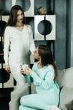 Deux beaux jeunes amis féminins dans le salon à la maison Photo stock