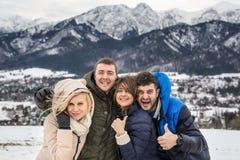 Deux beaux jeunes couples sur le fond du Tatra polonais photo stock