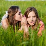 Deux beaux jeunes femmes et secrets de sourire heureux Images libres de droits
