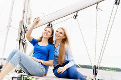 Deux beaux, jeunes filles attirantes buvant du café sur un yacht Images stock