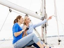 Deux beaux, jeunes filles attirantes buvant du café sur un yacht Image libre de droits