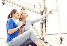 Deux beaux, jeunes filles attirantes prenant des photos sur un yacht Photo stock