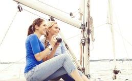 Deux beaux, jeunes filles attirantes prenant des photos sur un yacht Image stock