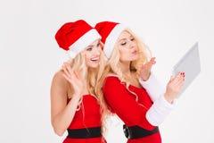 Deux beaux jumeaux de soeurs envoyant un baiser et à l'aide du comprimé Photos stock