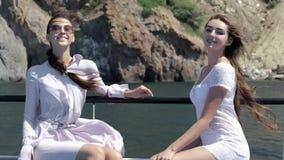 Deux beaux modèles dans des bains de soleil de lumière blanche se reposant à bord du bateau banque de vidéos