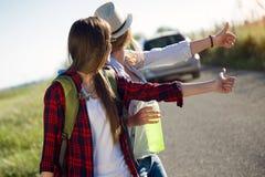 Deux beaux randonneurs de dames marchant sur la route Photos stock