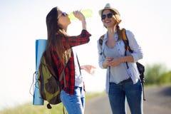Deux beaux randonneurs de dames marchant sur la route Images libres de droits
